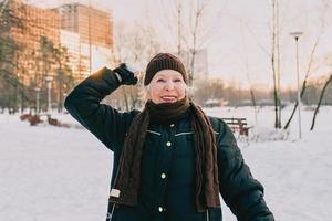 senior woman in hat and sporty jacket snowballing in snow winter park. Winter, age, sport, activity, season concept photo