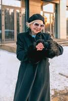 senior stylish woman in beret and elegant black coat and in medical mask walking outdoor and counting time till the end of pandemic. Lockdown, pandemic, protection concept photo