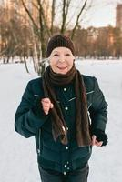 senior woman in hat and sporty jacket jogging in snow winter park. Winter, age, sport, activity, season concept photo