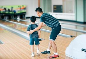 Father teaching son for play bowling at bowling club photo