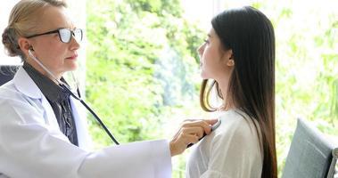 Médico con estetoscopio para examinar al paciente en su oficina en los hospitales foto