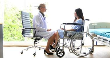 The doctors are asking and explaining about the illness to a female patient on wheelchair at a hospital photo