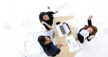 hombres de negocios y mujeres empresarias éxito y concepto ganador: equipo feliz con las manos levantadas celebrando el avance y los logros foto