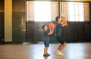familia asiática jugando baloncesto juntos. familia feliz pasando tiempo libre juntos en vacaciones foto
