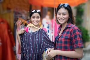 Two smiling young woman Asian with shopping and buy at outdoor photo
