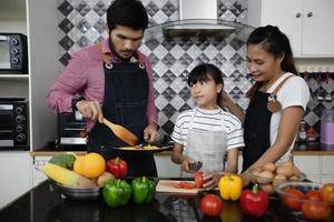 familia feliz tiene a papá, mamá y su pequeña hija cocinando juntos en la cocina foto