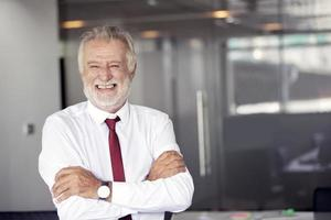 Happy handsome old businessman standing and smiling in office photo