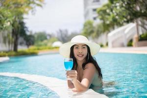 Women wear bikinis and drinking cocktails in the hot summer at the swimming pool. photo