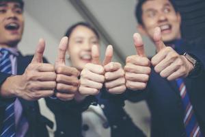 Sonriendo feliz empresario y empresarias celebrando el logro del éxito con el brazo levantado y mostrar el pulgar hacia arriba concepto foto