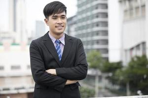 Happy handsome businessman standing and smiling  at outdoor photo