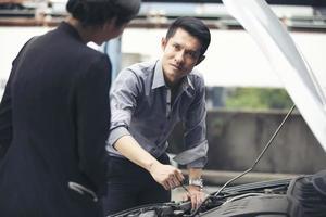 Los empresarios ayudan a las empresarias a comprobar y reparar coches rotos. foto