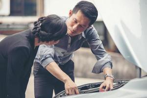 hombres de negocios ayudan a las mujeres de negocios a revisar y reparar autos rotos foto