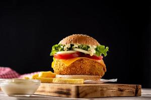 Crispy chicken burger with cheese and french fries photo