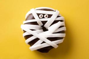 Mummy monster donut for Halloween party on yellow background photo