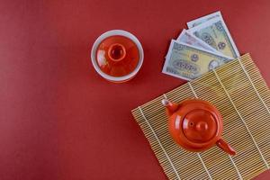 Celebrate Asian festival decorations Vietnamese New Year festive ceremony tea with Money Vietnamese dong on red background photo