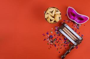Traditional celebration on Jewish holiday Purim in the hamantaschen cookies, noisemaker and mask carnival photo