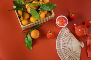 Feliz año nuevo chino lunar celebraciones con ceremonia juego de té en mandarinas un fondo rojo. foto
