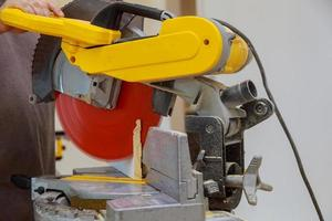 Close up of Circular saw cutting sharp rotary blade new baseboard woodwork photo