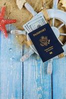 Sailor's captain's wheel time to travel concept sea shells in the beach sand over hundred dollar bills American Passport photo