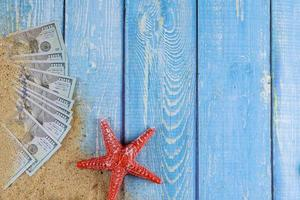 Red starfish on sand beach and US Dollar bill on blue wooden background photo