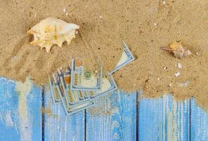Time to travel concept sea shells in the beach sand over hundred dollar bills photo