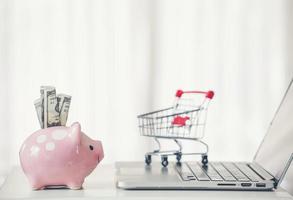 carrito de compras y hucha con laptop en el escritorio foto