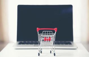 carrito de compras con laptop en el escritorio foto