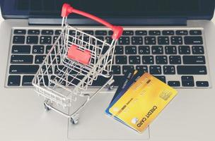 Shopping cart and credit card with laptop on the desk photo