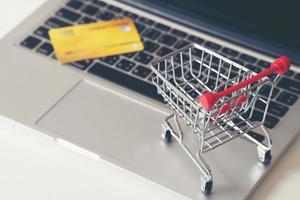 carrito de compras y tarjeta de crédito con computadora portátil en el escritorio foto