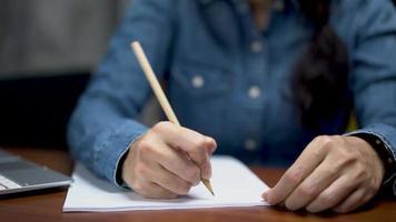 femme d'affaires utilise l'écriture au crayon de papier sur le bureau video