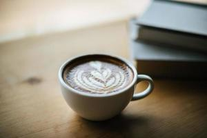 Latte art in coffee cup on the cafe table photo