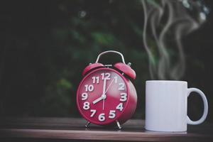 cup of coffee and white clock on on wood table  with bokeh photo