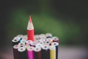 lápiz rojo que representa el concepto de destacar entre la multitud foto