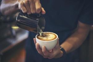 primer plano, de, manos, barista, hacer, latte, café, arte, pintura foto