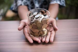 Hand  putting coins in jar with money stack step growing growth saving money photo