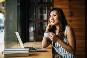 Bella mujer trabajando con ordenador portátil en la cafetería cafe foto