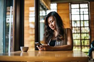 mujer sentada y jugando su teléfono inteligente en el café foto
