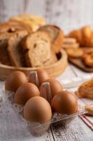 Eggs in a Plastic panels and bread that is placed on a white wooden plate. photo