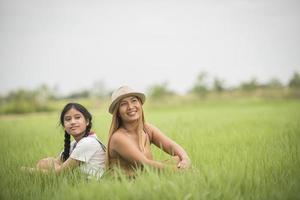 feliz madre con hija sentada en el parque de campo de hierba foto