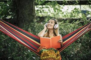Beautiful happy young woman with headphones listening to music and reading a book photo