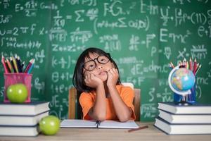 niña pensativa con libro cerca de una junta escolar foto