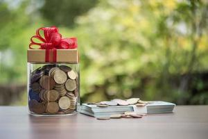 Gift box on dollars  in the glass jar photo