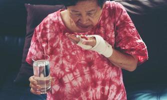 Senior asian woman take pill medicine on hand photo