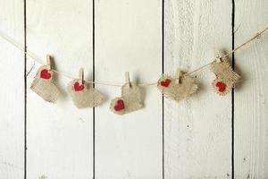 Feliz San Valentín corazones de arpillera colgando de una pared de madera foto