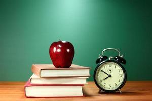 libros escolares, manzana y reloj en el escritorio en la escuela foto