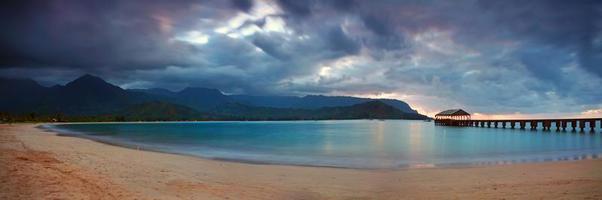 muelle hawaiano al atardecer con nubes dramáticas foto