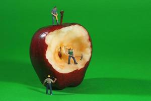 Trabajadores de la construcción en imágenes conceptuales con una manzana foto