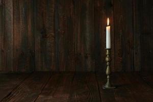 Vela encendida sobre un fondo rústico de madera vieja foto