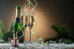 Two glasses of white champagne, open bottle and Christmas decorations photo