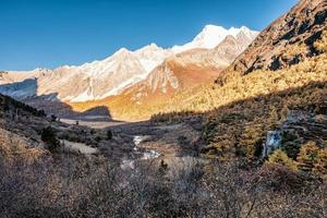 Holy mountain range with waterfall in pine forest in autumn photo
